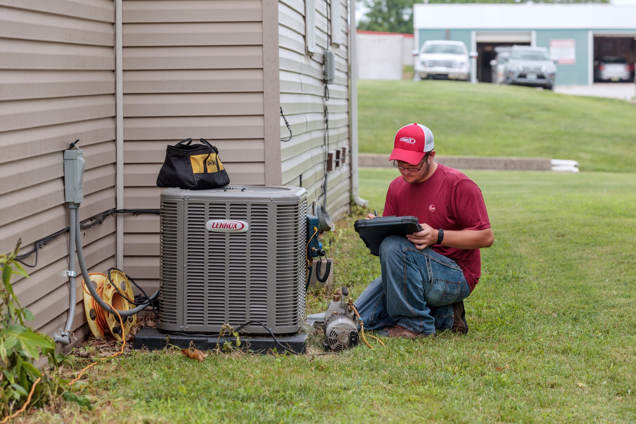 An HVAC professional is taking notes outside of a customer's house by an A/C unit