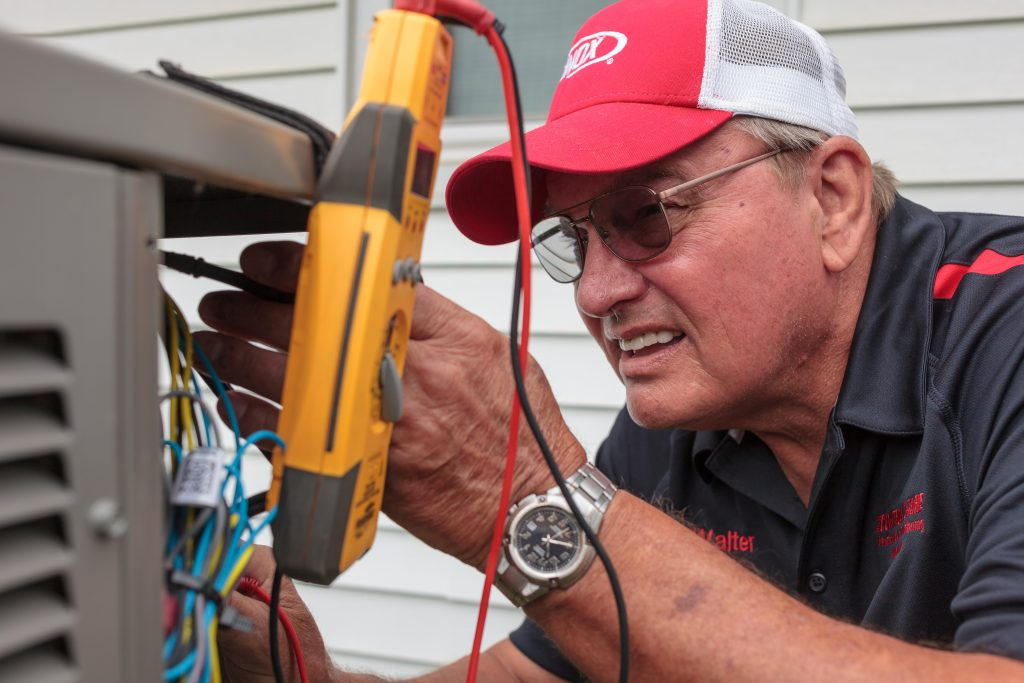 A Controlled Aire employee is attempting to fix a customer's A/C unit.