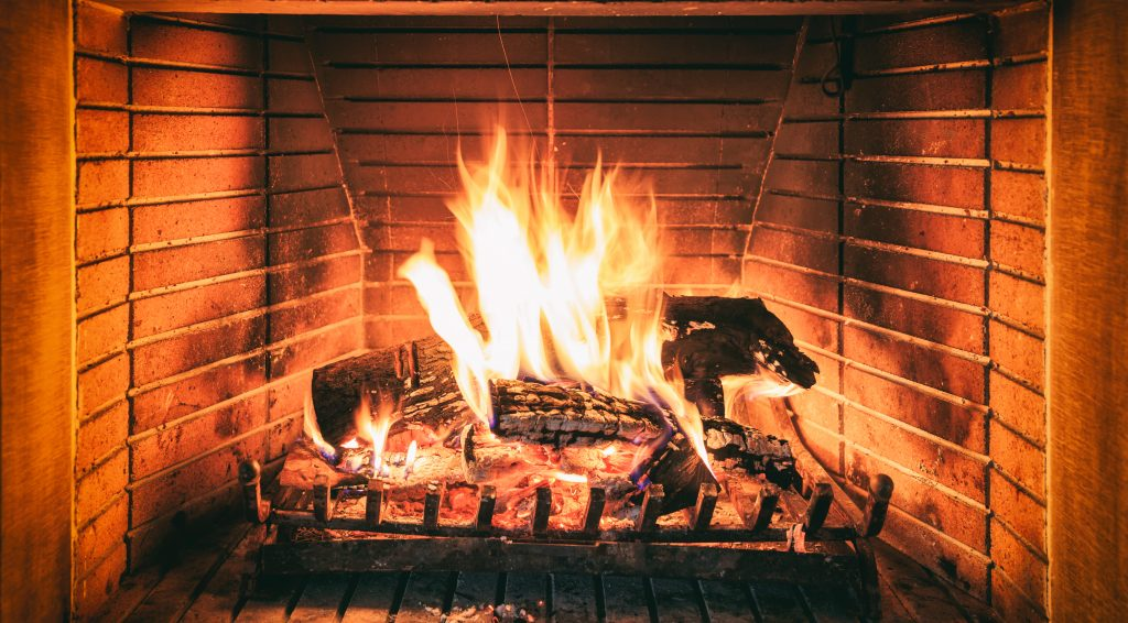 Logs burning in a home fireplace with a large flame