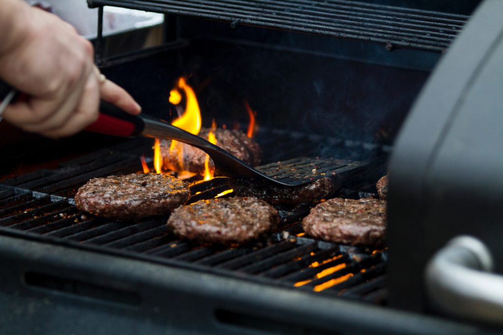 Burgers being grilled on an outdoor charcoal grill