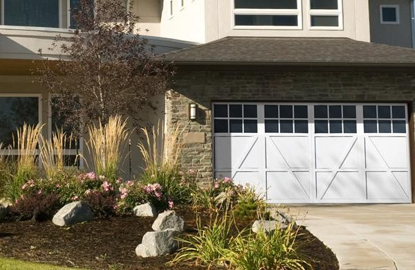 A lovely white residential garage door on a beautiful clothes