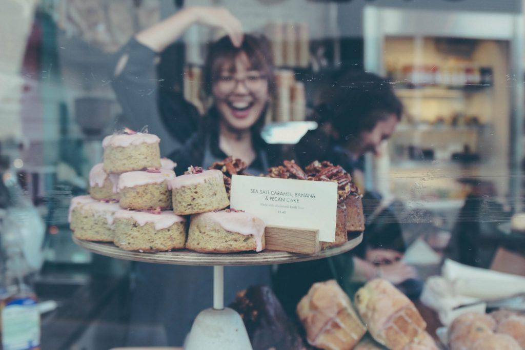 photo of donuts and woman through store glass