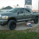 Girl looking under gray pickup truck at KB Tire & Auto