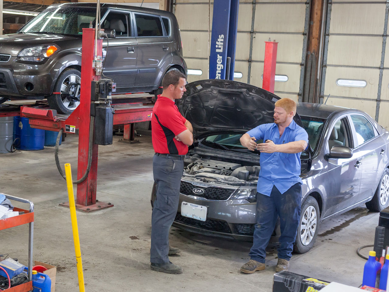 Two automotive technicians discussing repairs at KB Tire & Auto located in Moberly, MO