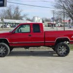 Side view of red pickup truck at KB Tire & Auto