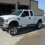 Side view of white Ford pickup truck at KB Tires & Auto