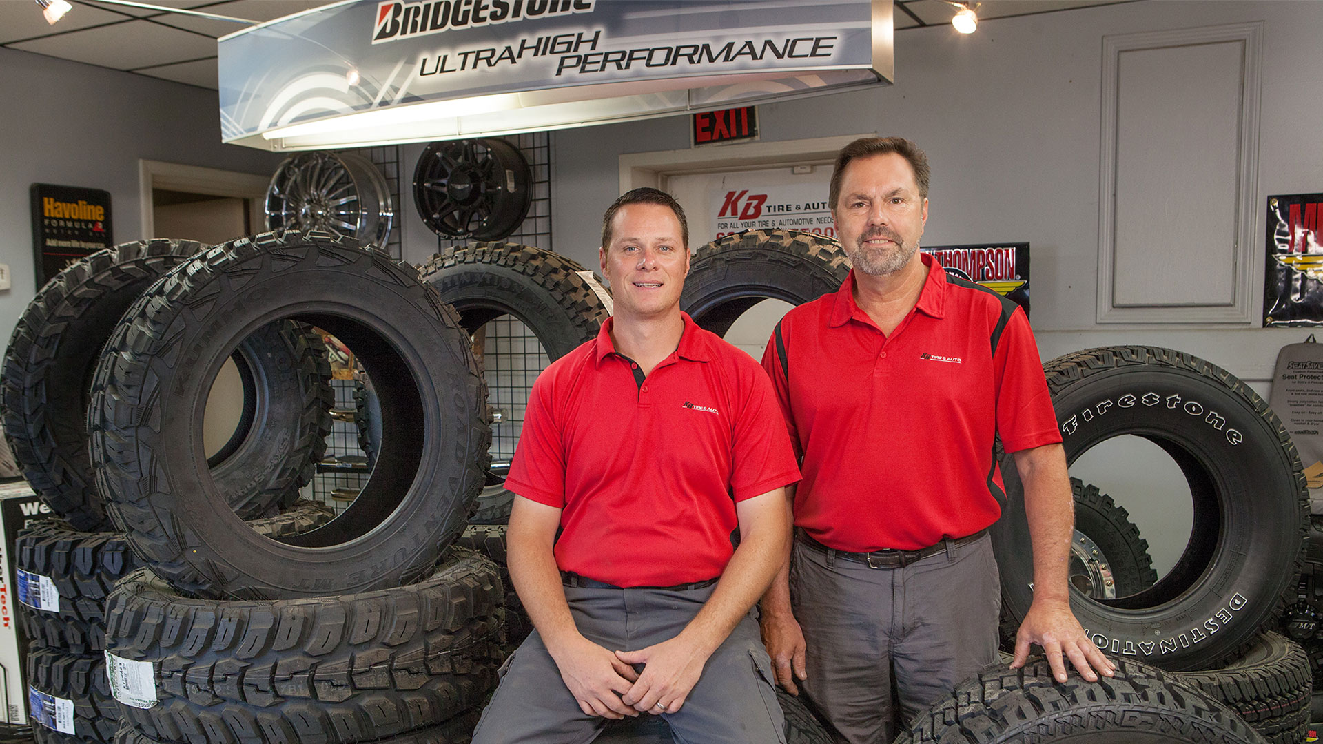 Owners of KB Tire & Auto posing with tire display
