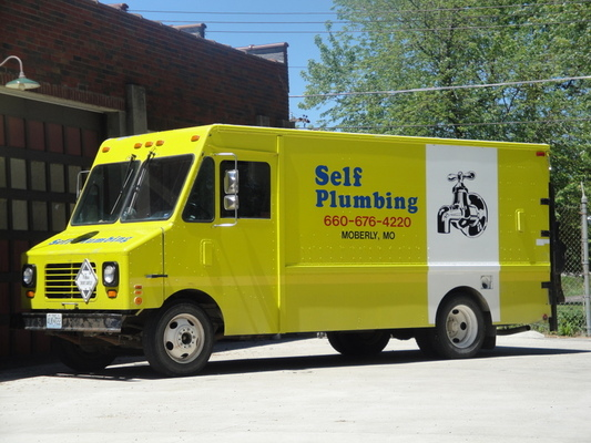 Yellow Self Plumbing service vehicle parked in a parking lot
