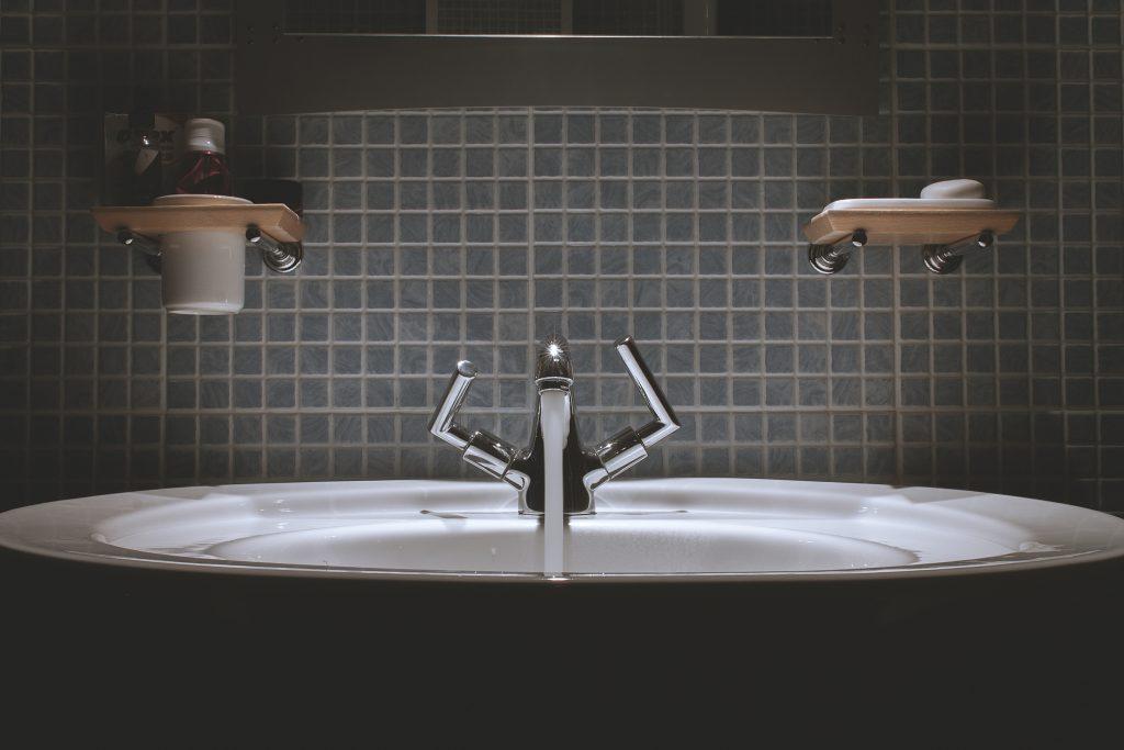 Residential plumbing - bathroom sink against blue tile backsplash