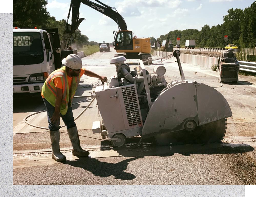 worker operating a slab saw on a highway project