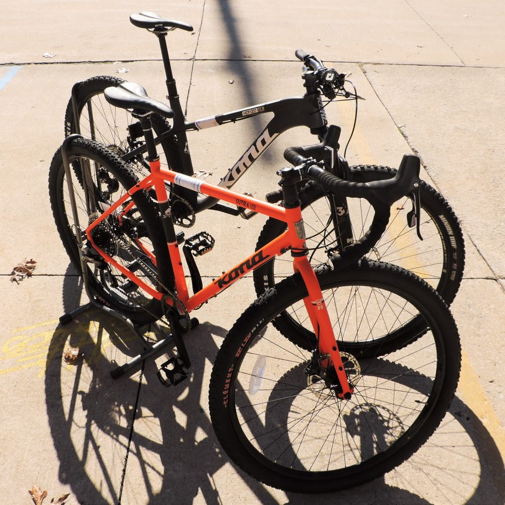 Two Kona bikes, back is black front bike is orange