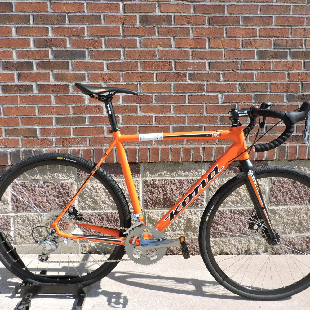 Orange Kona bike in front of brick wall