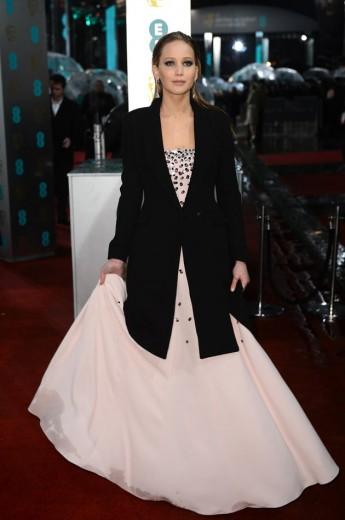 Jennifer Lawrence, a garota Dior, chegou assim, com um maxipaletó por cima do look