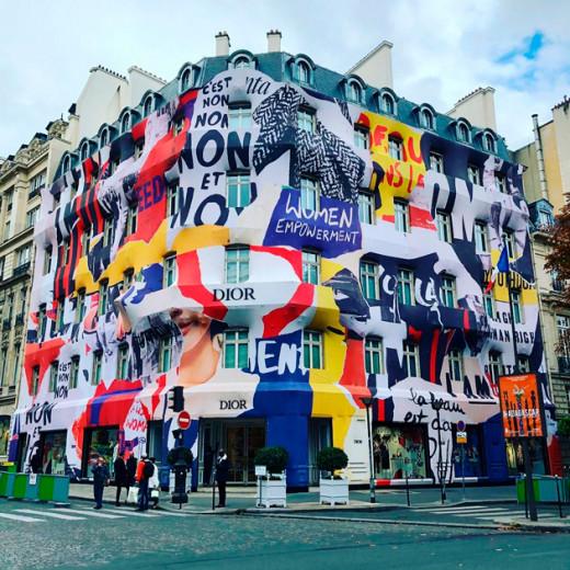"""A Dior """"vestiu"""" sua famosa butique da avenida Montaigne, em Paris, com grafismos e protestos feministas que remetem aos eventos de maio de 1968! Vem ver!"""