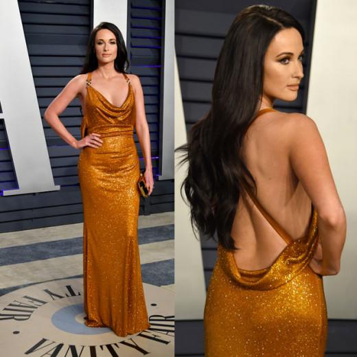 Puro luxo nesse modelo dourado Versace de Kacey Musgraves! Vem ver mais fotos dos melhores looks das celebs com costas de fora!