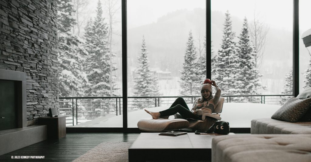 Girl drinking coffee on couch with snow outside