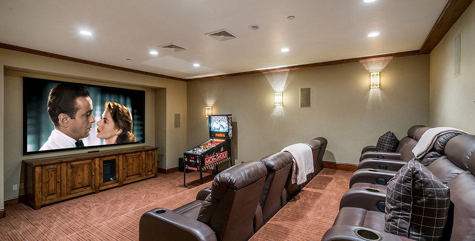 Large home theater room with a pin ball machine and recliners in a kid-friendly vacation rental