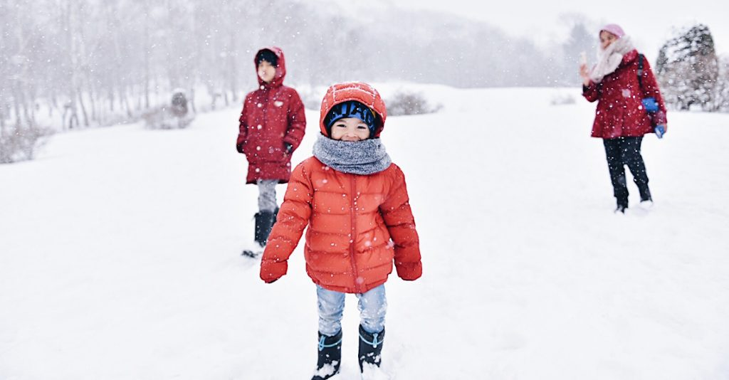 Woman and two kids walking in the snow