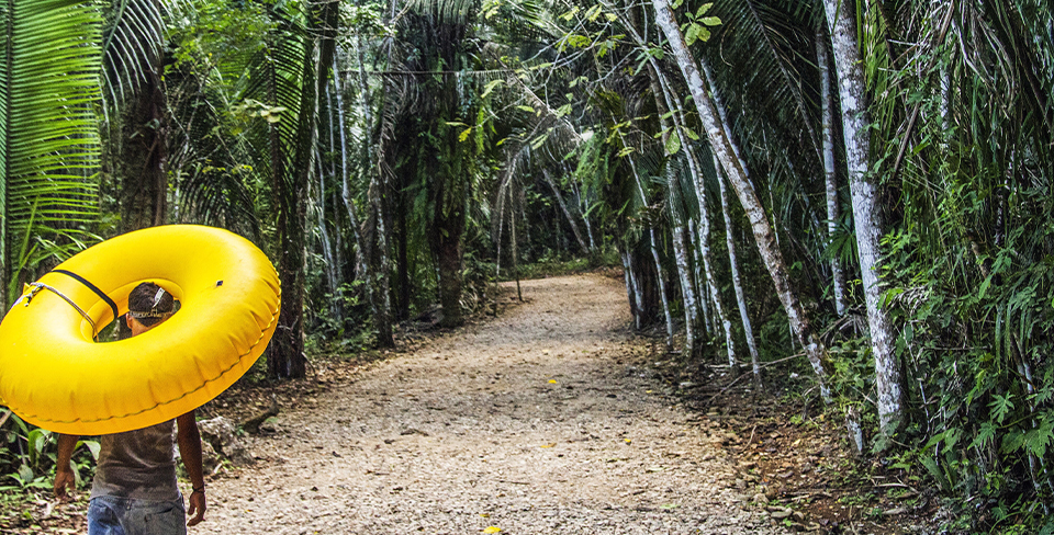 Boy walking through the forest in Belize with a yellow inner tube