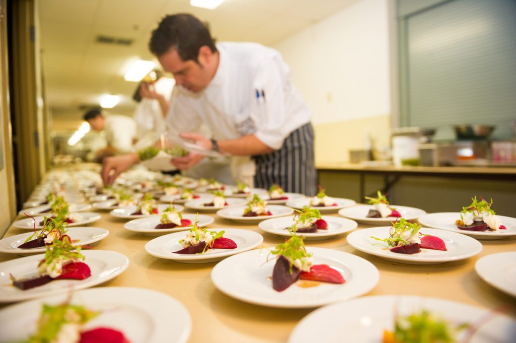 A chef plating up meals ready for service at Cornucopia