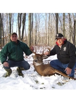 Two men in the snow holding up a deer.