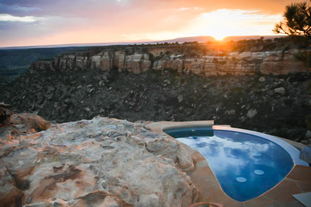 A pool with rocky hills in the background in front of a sunset.