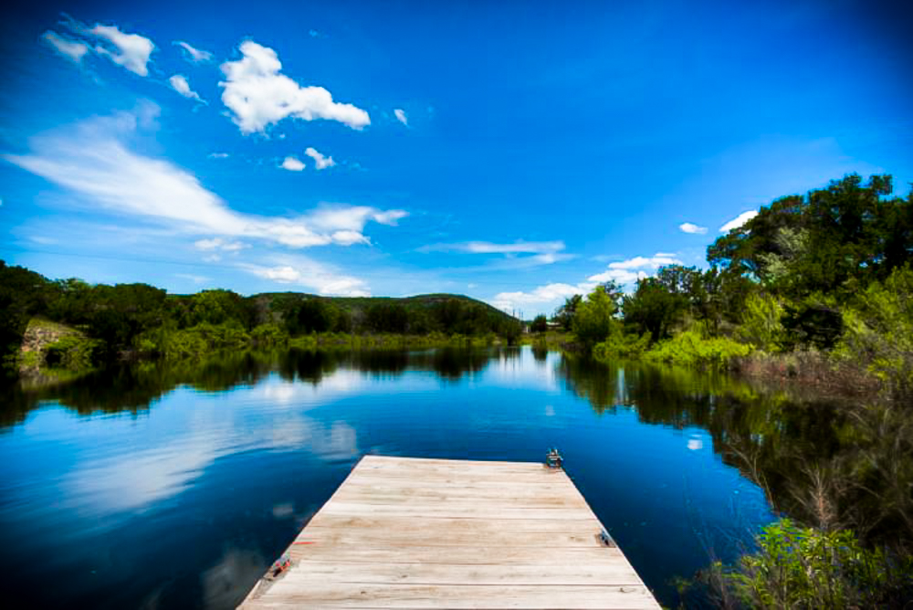 A blue lake surrounded by trees with a dock protruding atop the water.