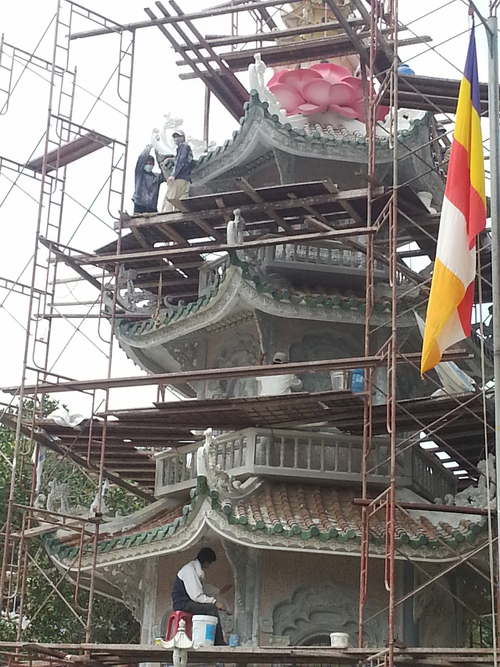 Temple work. vertical, architecture, workers, scaffolding, towers, buddhism, flags, vietnam, temples, pagodas, phuocthanh. buy photo
