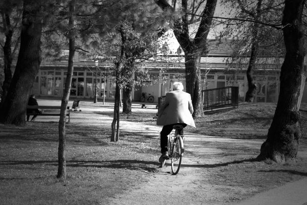 a man riding a bike down a street. bw, cycling, blackwhite, croatia, varaždin, ilobsterit. buy photo
