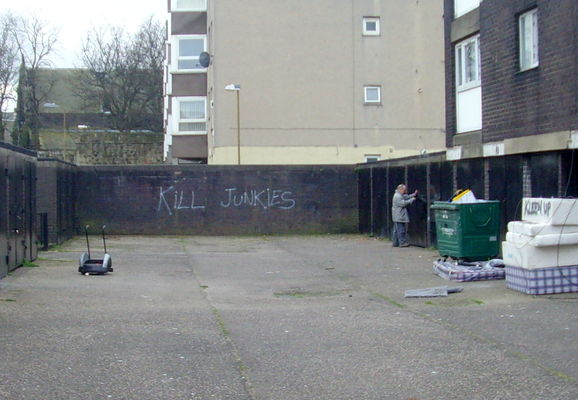 Grim scene in Leith, Scotland. uk, man, writing, concrete, graffiti, scotland, alley, edinburgh, grim, candid, country, north, courtyard, scene, flats, rubbish, council, leith, slogan, share, scots, garages, ©2013tonyworrall. buy photo