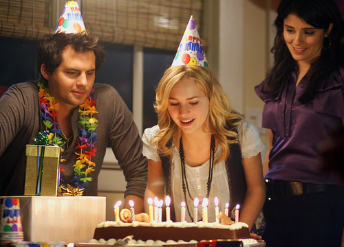 Life Unexpected Season 1 Episode 1 (still) Lux about to blow out the candles on her birthday cake. episodic. buy photo