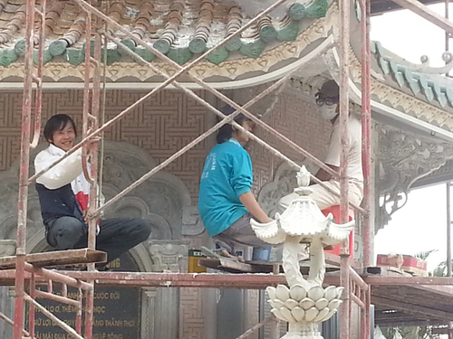 Finishing touches. architecture, workers, scaffolding, smiles, vietnam, temples, pagodas, craftsmen, facemasks, finishingtouches, buildingsites, phuocthanh. buy photo