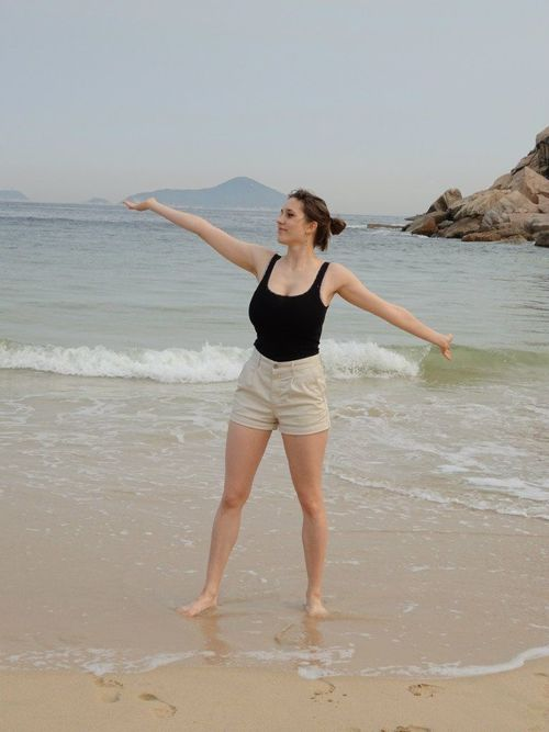a woman is standing on a beach holding a surfboard. buy photo
