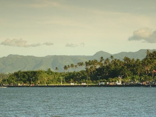 a boat is in the water near the mountains. buy photo
