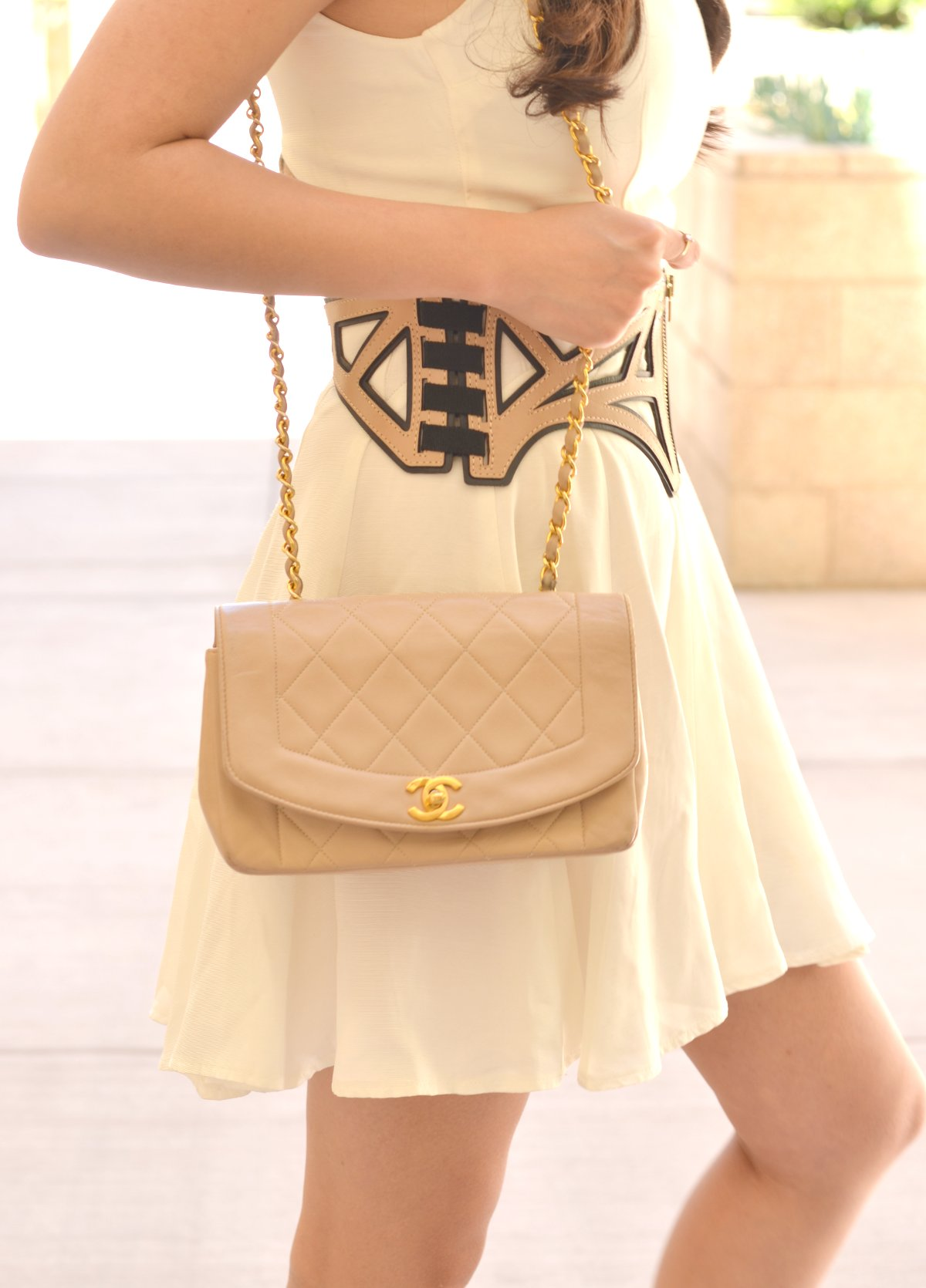 beige chanel bag on person with herve leger corset harness