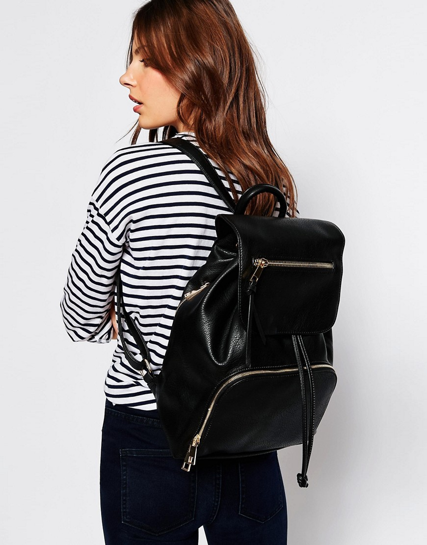 Aldo black with gold hardware flap backpack on body being worn