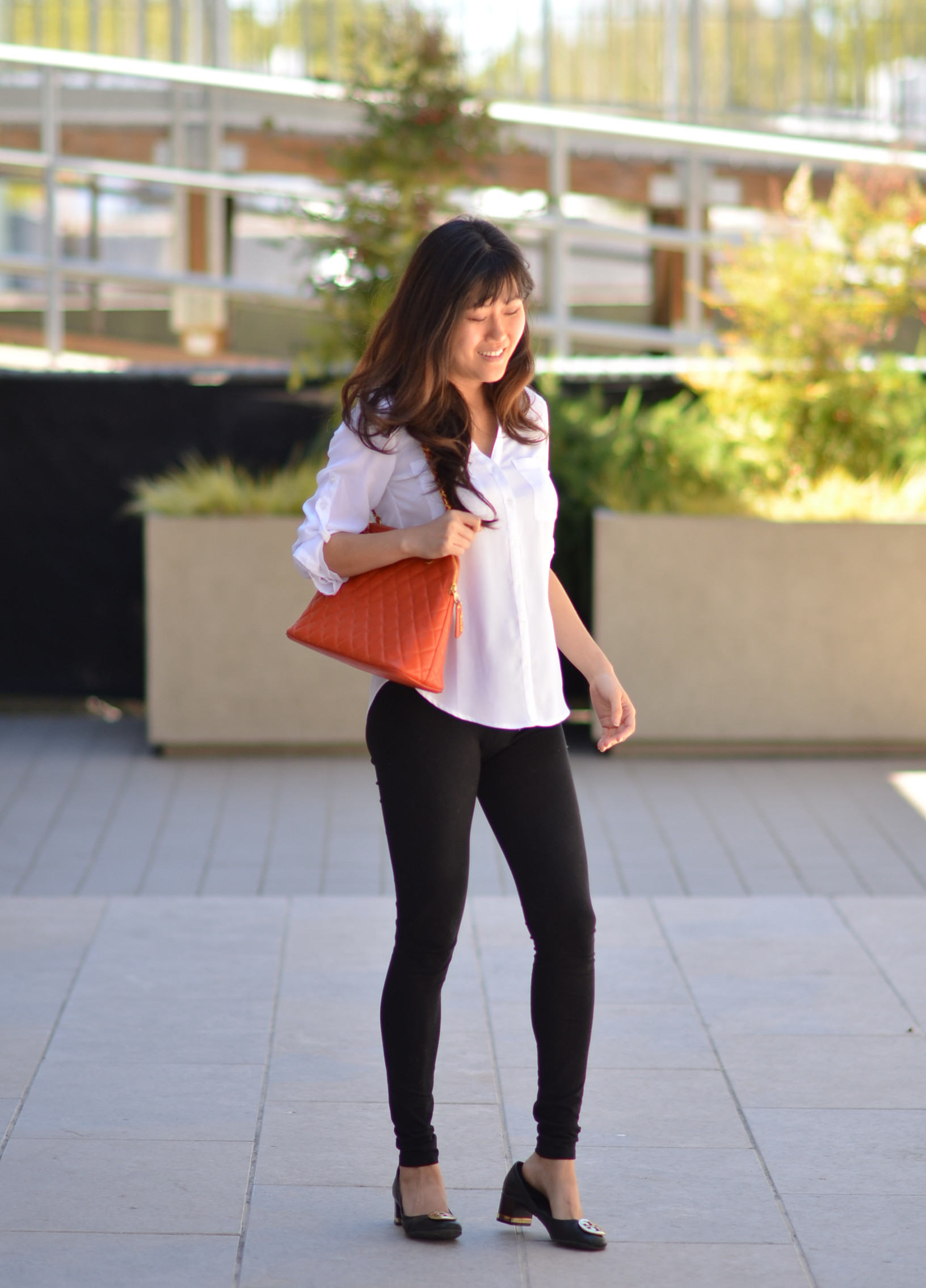 simple neutral outfit with colored handbag