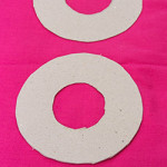 Cut out two identical circles of cardboard with a small hole in the middle of each circle.