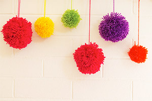 Make a variety of pom poms in different colours and sizes to create a decorative feature.