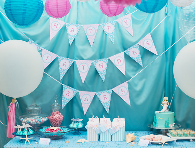Mermaid Party Styling Ideas: Blue satin is a great backdrop with Party Bunting, Balloons and Pink Pom Poms