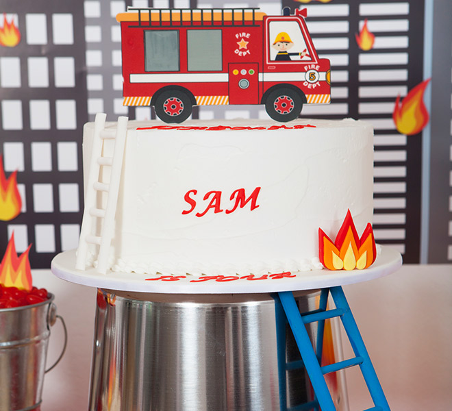 Fireman Party Birthday Cake by Burnt Butter. We sat the cake on a top of a tin bucket and painted a mini ladder (from a pet store) blue to add a little fun to the display. So easy!