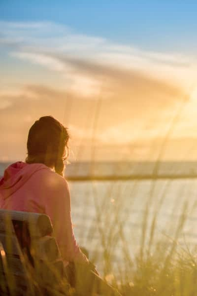 woman on bench overlooking water with title text overlay - Thanks for Nothing