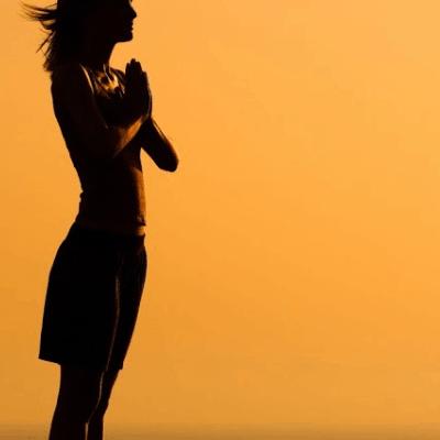 image of woman praying at sunset