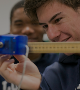 2 Loyola High School students measuring something in a science lab