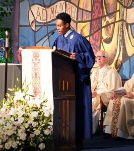Loyola High School student reading from pulpit during a ceremony