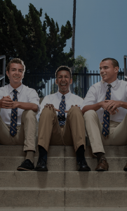 4 Loyola High School students sitting on the steps in white shirts and ties