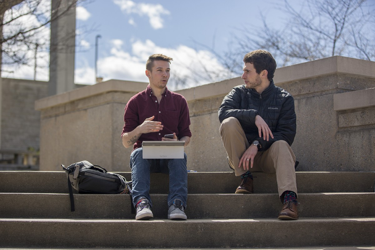 two students sitting outside on the steps, talking.