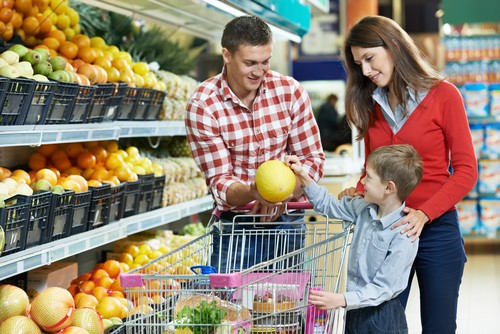 a young couple entertains their son in the grocery store