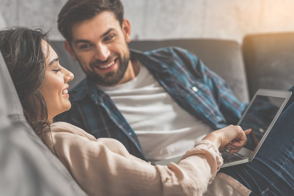 couple on sofa searches the internet