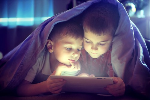 two children watch a video on a tablet while hiding under a blanket